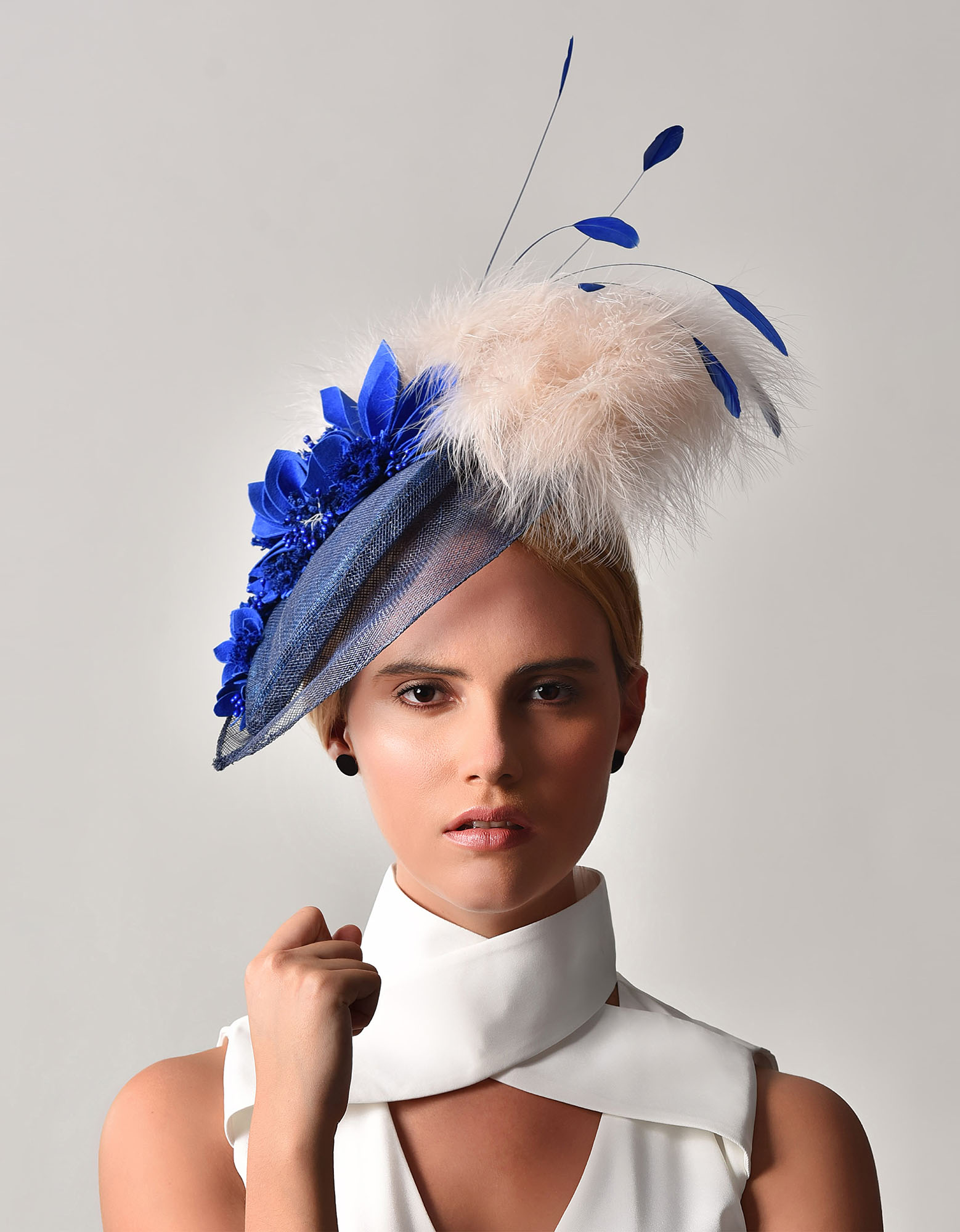 Royal blue sinamay tear drop accompanied with suede and tweed flowers, finished with honey feather plume and blue coque drops.